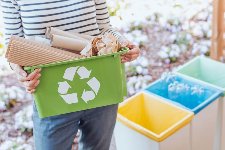 Девушка держит в руках зеленый контейнер с символом переработки отходов, который заполнен бумагой и картоном. На заднем фоне стоят три разноцветных контейнера для раздельного сбора мусора.